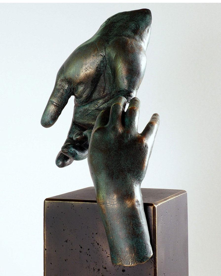 La mano del padre en bronce